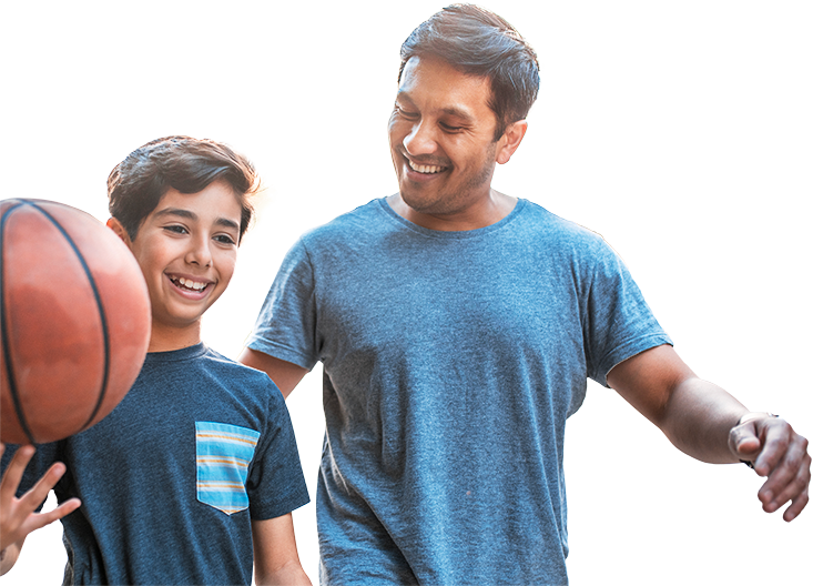 Smiling father in blue shirt beside smiling son holding basketball